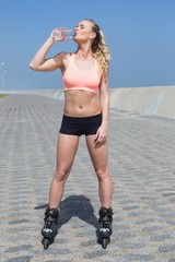 Fit blonde drinking water in roller blades