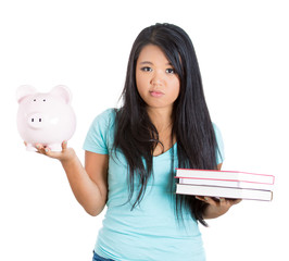 woman balancing piggy bank in one hand books in another