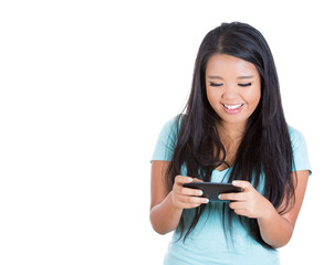 Happy teenager girl texting on her smart phone