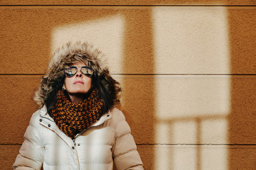 Woman with Winter Clothes Against an Orange Wall