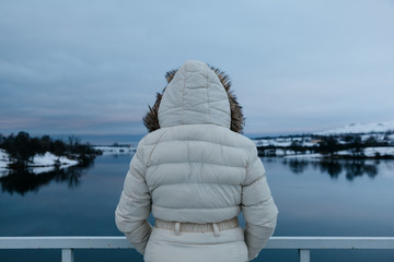 Back View of a Woman Looking at the Frozen Lake at Twilight