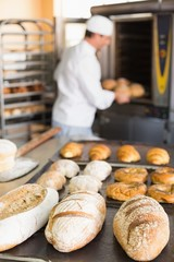 Happy baker taking out fresh loaves