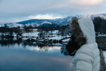 Side View of a Woman Looking at the Frozen Lake at Twilight