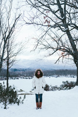 Woman Sating on a Snowy Landscape at a Frozen Lake
