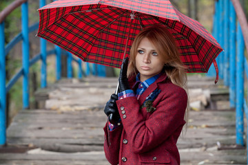 Beautiful blonde woman stands on bridge under umbrella