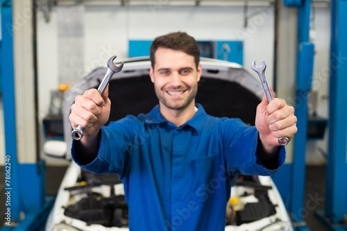 canvas print picture Mechanic holding pair of wrenches