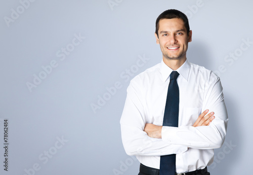 Happy smiling young businessman, against grey - 78062484
