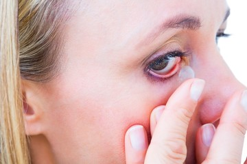 Close up of blonde applying contact lens