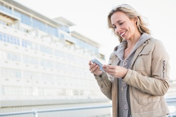 Smiling blonde standing and text messaging