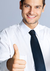 Smiling businessman with thumbs up gesture