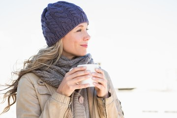 Thoughtful blonde in warm clothes holding hot beverage