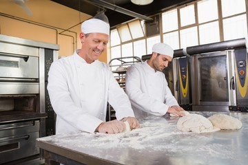 Smiling bakers kneading dough at counter