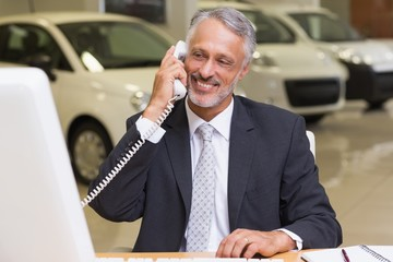 Smiling businessman using phone in front of computer