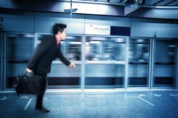 Asian businessman in a subway, motion blur.