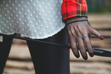 Horsewoman hand in fishnet glove holding a stack for riding