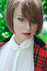 Close-up portrait of beautiful young woman in horsewoman suit in