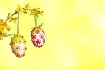 Zweig mit Ostereiern auf Hintergrund hellgelb