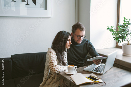 Couple working in cafe with tablet, laptop, smartphone, notepad