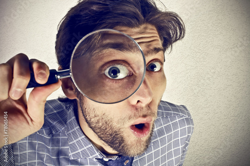 Businessman looks through a magnifying lens - 78065454