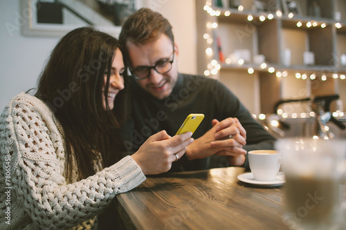 Young couple in cafe sitting with smartphone and coffee - 78065458
