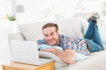 Happy man lying on sofa using laptop