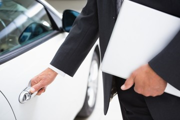 Man holding a car door handles while holding clipboard