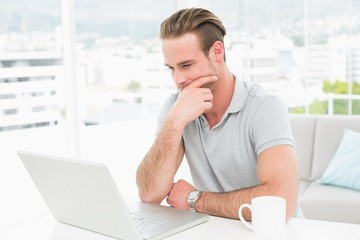 Thoughtful casual businessman working with laptop