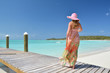 Girl at the wooden jetty looking to the ocean. Exuma, Bahamas
