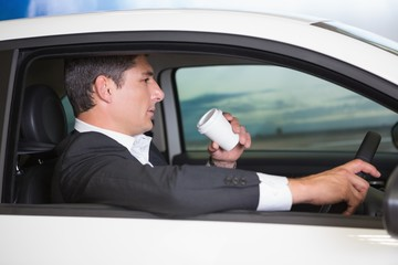 Serious businessman drinking coffee while driving