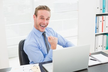Excited businessman sitting at his desk cheering