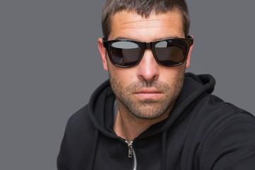 Criminal with sunglasses looking at camera