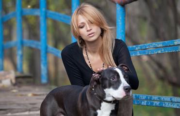 Pretty blonde woman stroking a purebred dog