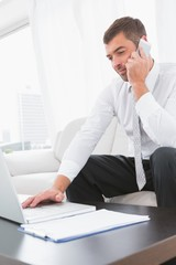 Smiling businessman on a phone with a laptop at home