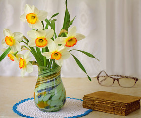 Blossoming narcissuses in a vase on a table.