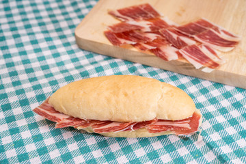 Side view of Serrano ham sandwich over checkered tablecloth