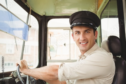 Smiling driver driving the school bus