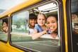 Leinwandbild Motiv Cute pupils smiling at camera in the school bus