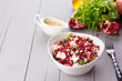 Healthy salad with pomegranate seeds, almond, feta cheese and