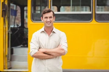 Smiling bus driver standing with arms crossed