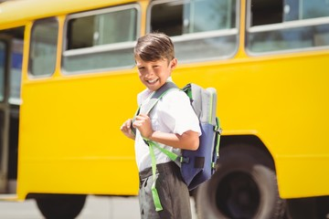 Cute pupil walking to the school bus