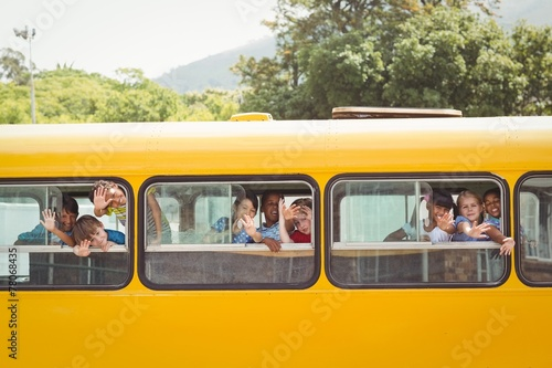 Cute pupils smiling at camera in the school bus - 78068435