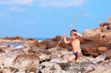 boy with bamboo spear pretends like he is aborigine on island