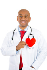 Happy smiling male doctor with stethoscope holding heart