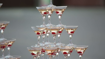 Pyramid from glasses with champagne with cherry in glasses