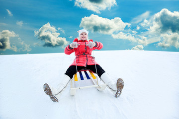 screaming child in red clothes rides the hills on sleds