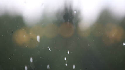 There are heavy wind and rain outside a window