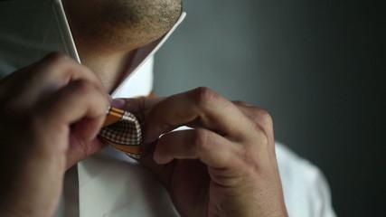 A man by the window wears bow tie