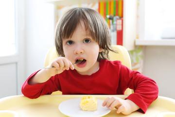 2 years boy eating scrambled eggs. Healthy nutrition