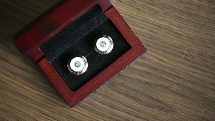Cufflinks at wooden background