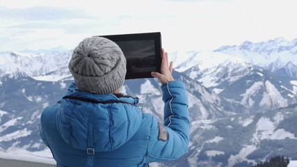 Woman hiker taking photo with digital tablet, Alps